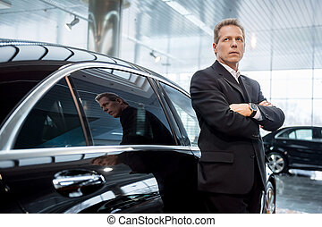 Dreaming of a new car. Thoughtful grey hair man in formalwear leaning at the car and looking away