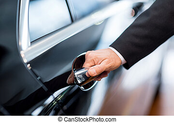 Hand on handle. Close-up of man in formalwear opening a car...