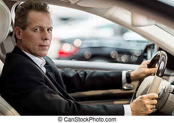Confident drive. Side view of confident senior man in formalwear sitting in car and looking at camera