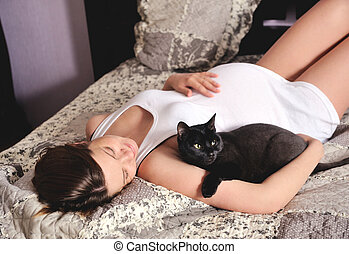 Smiling pregnant woman with cat at home. - Young smiling...