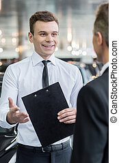 Salesman and customer. Handsome young classic car salesman talking to a customer and smiling