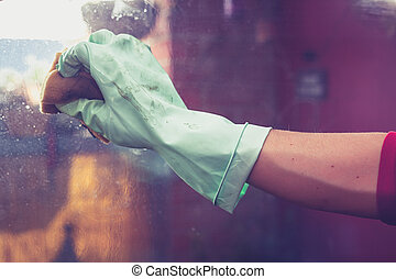 Hand wearing rubber glove is cleaning windows