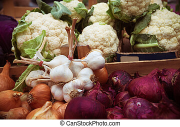 organic food on the market, garlic, onion, and cauliflower
