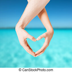 woman and man hands showing heart shape - love, summer...