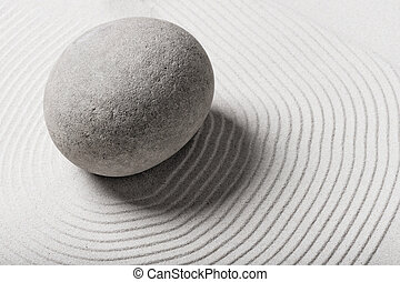 stone in the sand and circles around him
