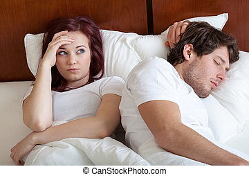 Riser in bed with her sleeping  husband at the morning