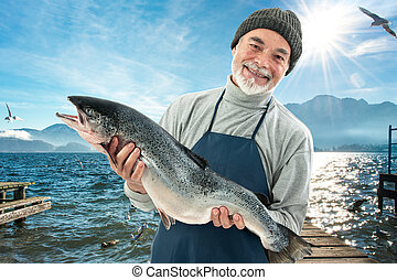 Fisher holding a big atlantic salmon fish in the fishing...