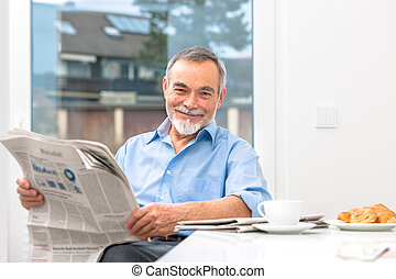 Senior man with newspaper - Happy senior man at breakfast...