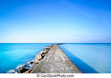 Concrete and rocks pier or jetty on blue ocean water