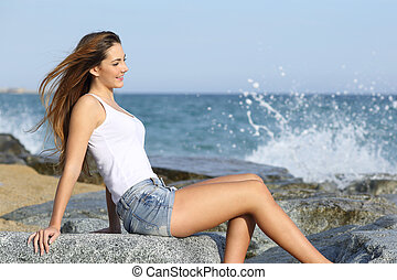 Beautiful woman enjoying the wind on the beach with the sea...