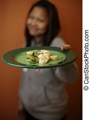 Girl offering you plate of fruit - The scene can be...