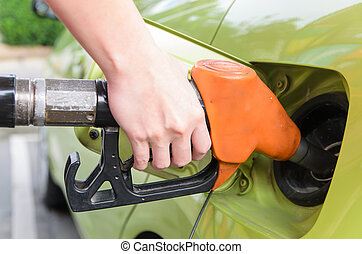 Women hold Fuel nozzle to add fuel in car at gas station