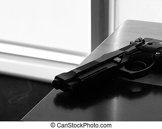 hand gun - a hand gun lying on a table in black and white