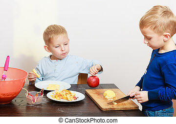 Boys brothers cutting apple at home - Blond boys children...