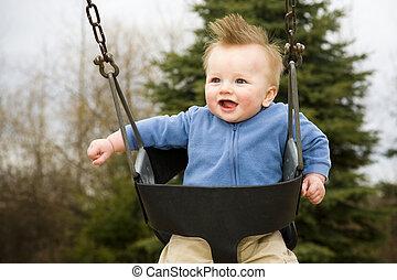 Happy Boy on Swing - A portrait of a happy boy on a swing in...