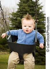 Happy Boy on Swing - A portrait of a happy boy on a swing in...