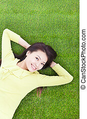 beautiful young woman laying down in park