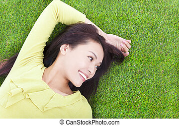 young woman lying and looking side in a meadow