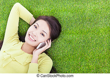 pretty girl talking over the phone in a meadow