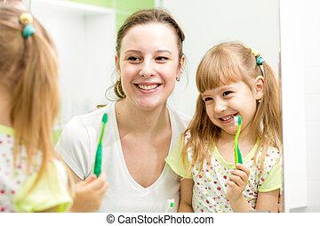 mother teaches kid brushing teeth