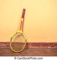 Vintage tennis racket against a wall