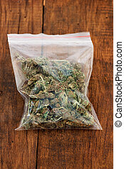 Marijuana - Big plastic bag of weed or marijuana on wooden...