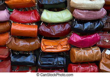 Display of leather purses of various colors, in an outdoor...