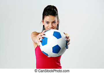 Young happy sport woman giving you a soccer ball on gray...