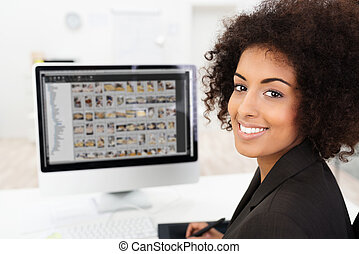 Smiling businesswoman editing photographs - Smiling African...