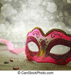 Pink carnival mask with glittering background