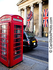 Red phone booth and local taxi in motion. London