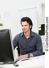 Businessman working at his computer - Handsome young...