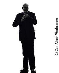 senior business man tying up necktie silhouette