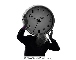 senior business man holding time clock silhouette