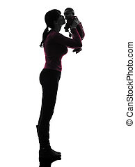woman mother holding kissing baby silhouette - one caucasian...