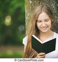 young teenage girl reading book near tree, summertime...