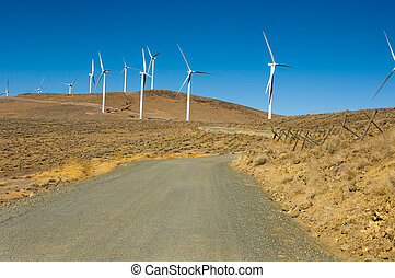 Gravel road among wind turbines - Road leading to a wind...