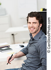 Young businessman working at his desk holding a pen or...