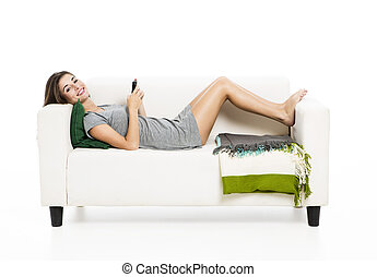 Woman sending sms - Beautiful woman on a sofa with a...