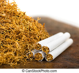 tobacco and cigarettes - pile of tobacco and hand-rolled...