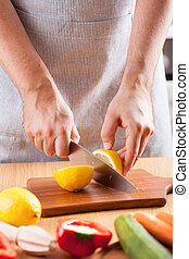 chef hands cutting lemon in kitchen
