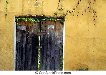 Rustic door, yellow wall, Antigua, Guatemala. - Old wooden...