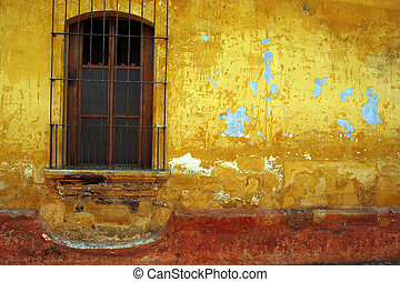 Barred window, yellow and red wall, Antigua, Guatemala. -...