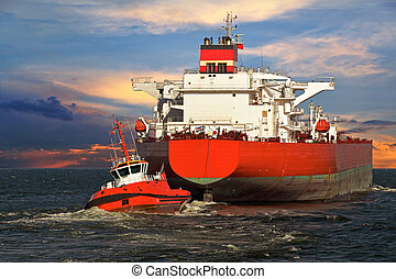 Tugboat towing a ship - Tug boat towing a tanker ship at sea...