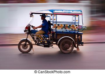 Motion blur TukTuk - TukTuk speeds past in Vientiane, Laos.