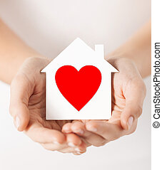 hands holding white paper house - charity, real estate and...