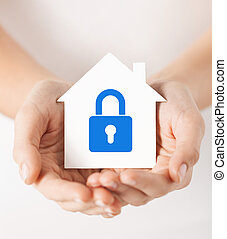 hands holding paper house with lock - real estate and family...
