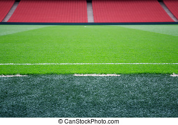 Pitch side - Empty football pitch with red seating,...