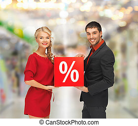 smiling man and woman with percent sign - sale, shopping and...