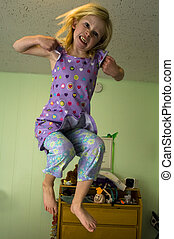 Angry girl jumping on a bed - Angry young girl jumping on a...